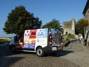Le minibus de la ville avec le château de Domfront en arrière-plan