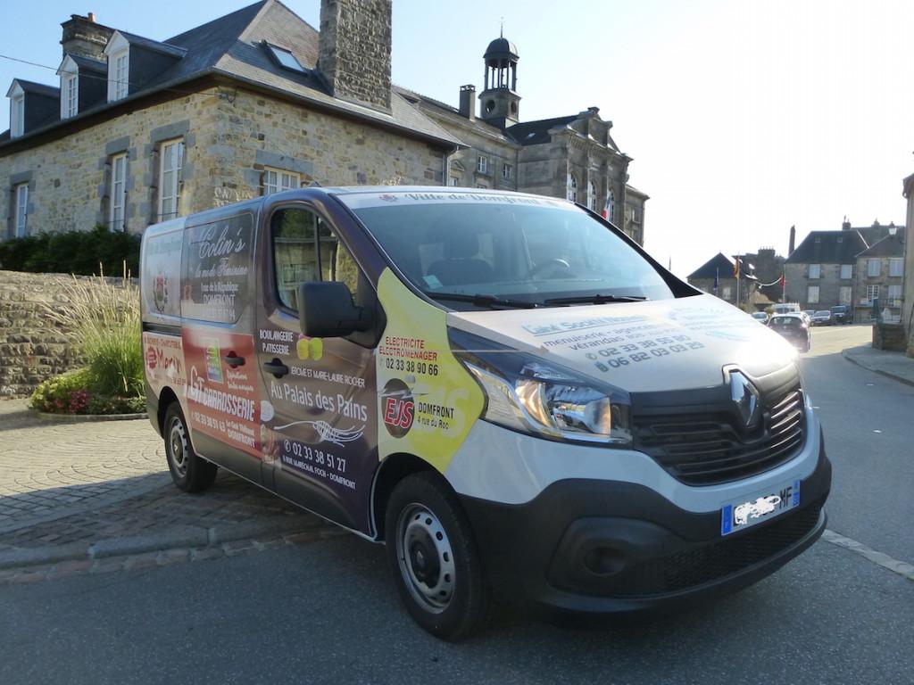 Le minibus de la ville garé sur la place devant l'office de tourisme et en arrière-plan la mairie de Domfront.